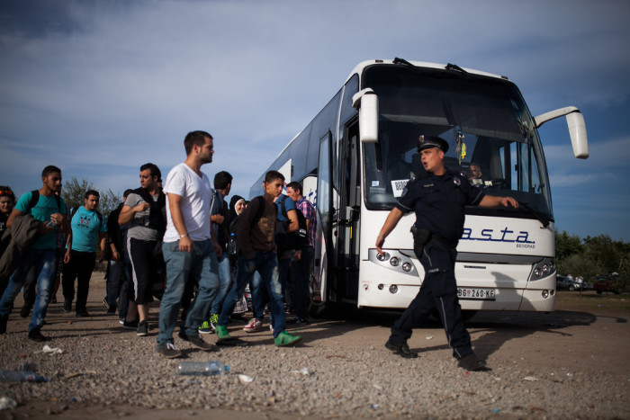 Serbian policemen directs asylum seekers from refugee camp to buses leaving for Horgos. Photo: Márton Magócsi