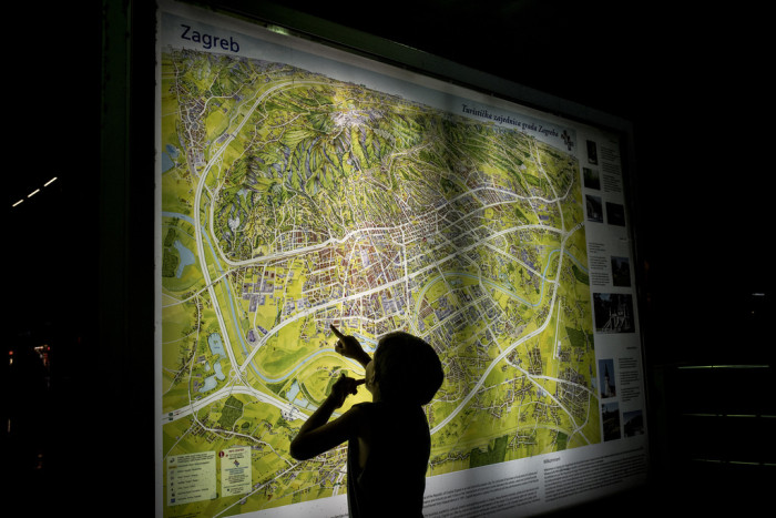 A young boy studies a map of Zagreb as his parents buy tickets to Vienna  Photo: D. András Hajdú