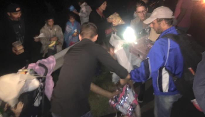 Volunteers distributing clothing to shivering asylum seekers