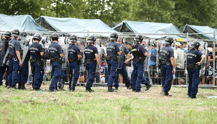 Hungarian riot police watching over refugee camp in Röszke  Photo: Origo.hu
