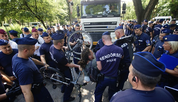 Budapest, 2016. július 6. Rendõrök viszik el a Ligetvédõk nevû civil mozgalom egyik aktivistáját a városligeti Hungexpo irodaházaknál 2016. július 6-án. Az épületek bontását megkezdték, a hatóságok kiürítették a Liget Budapest projekt ellen tiltakozó aktivisták által elfoglalt területet. MTI Fotó: Balogh Zoltán
