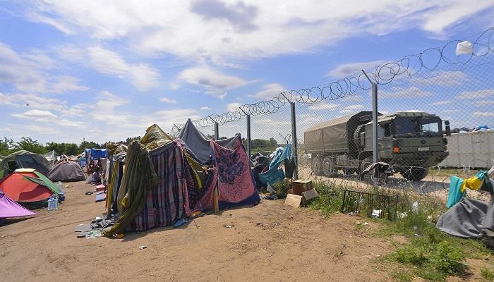 Kelebia, 2016. július 5. Migránsok sátortábora a vajdasági Kelebiánál, a szerb-magyar határ közelében, a határvonalon húzódó magyar védõkerítés mellett 2016. július 5-én. A határ szerbiai oldalán az Európai Unió nyugati államaiba igyekvõ több száz migráns táborozik arra várva, hogy valahogyan bejusson Magyarországra. Ezen a napon éjféltõl mélységi határõrizetet vezettek be a magyar hatóságok a szerb és a horvát határ mentén. Azokat a migránsokat, akiket a határtól számított nyolc kilométeres távolságon belül elfognak, visszakísérik a kerítésen található kapukig, és útbaigazítják a legközelebbi tranzitzóna felé. Megduplázták a határ védelemben részt vevõ katonai és rendõri erõk létszámát, így folyamatosan egy 6-10 ezres állomány védelmezi az érintett határszakaszt. MTI Fotó: Molnár Edvárd